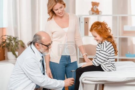 side view of senior doctor examining little girl with reflex hammer in clinic