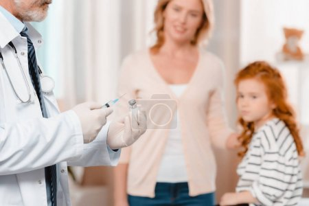 selective focus of doctor in medical gloves with syringe going to make injection to little girl in clinic