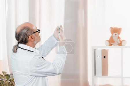 side view of senior doctor in eyeglasses and medical gloves holding syringe in clinic