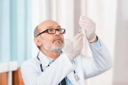 portrait of senior doctor in eyeglasses and medical gloves holding syringe in clinic