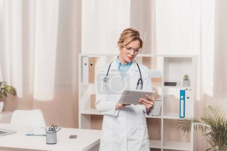 Photo pour Portrait de généraliste en blouse blanche à l'aide de tableau en clinique - image libre de droit