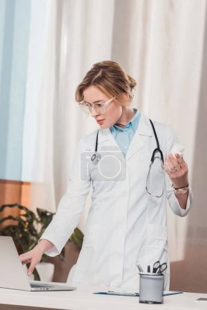 portrait of doctor in white coat with medicines in hand using laptop at workplace in clinic