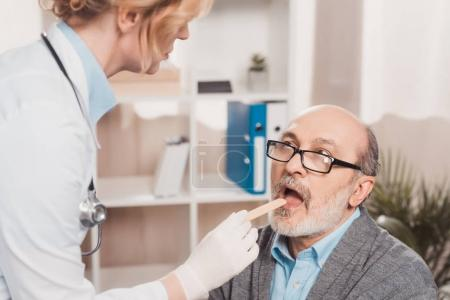 selective focus of doctor in medical gloves checking patients throat in clinic