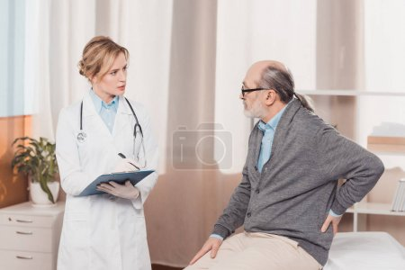 Photo pour Médecin en manteau blanc avec bloc-notes à l'écoute des patients plainte à la clinique - image libre de droit