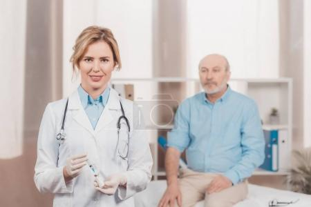 selective focus of doctor holding syringe for injection with senior patient behind in clinic