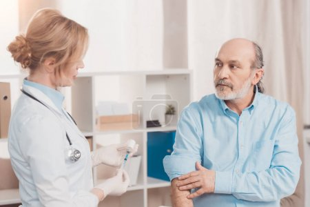 doctor in white coat going to make injection to senior patient in clinic
