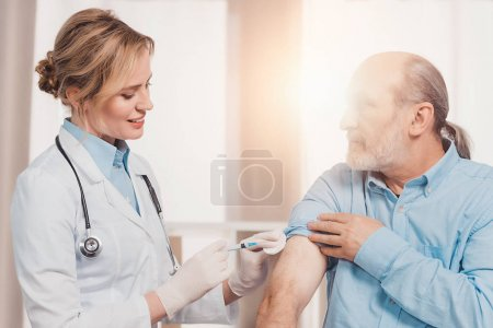 smiling doctor in white coat making injection to senior patient in clinic