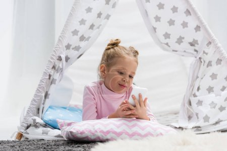 adorable little kid using smartphone in handcrafted teepee at home