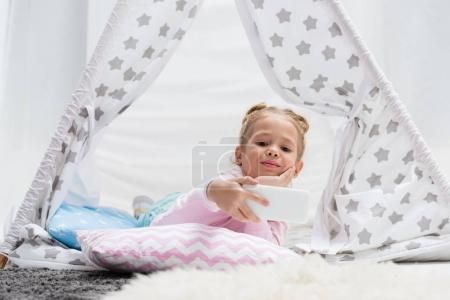 adorable little kid taking selfie in handcrafted teepee at home