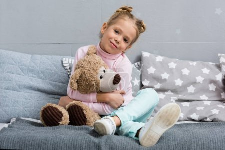 smiling little kid sitting in bed with teddy bear
