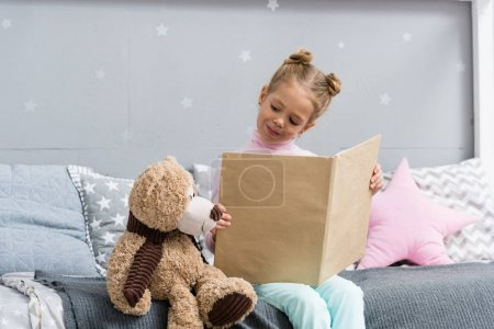 adorable little kid reading book in bed with teddy bear