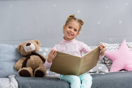 happy little kid reading book in bed with teddy bear