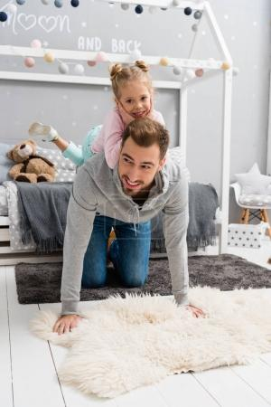 daughter riding on fathers back in kid bedroom