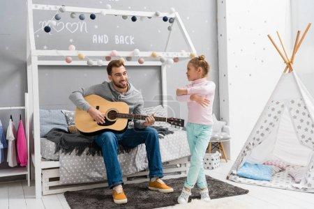 Photo pour Jeune père jouer de la guitare pour fille dans la chambre alors qu'elle danse devant lui - image libre de droit
