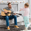 happy father playing guitar for daughter in bedroom while she dancing in front of him
