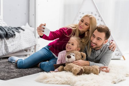 happy young family taking selfie while lying on floor together