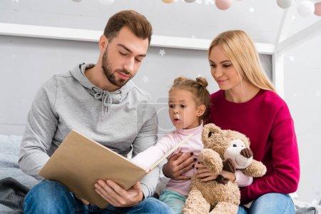 Photo pour Heureux jeune livre de lecture de famille ensemble - image libre de droit