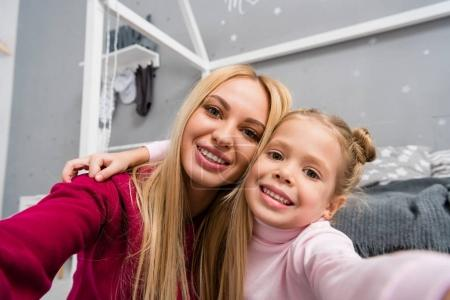 Photo for Close-up shot of young smiling mother and daughter looking at camera - Royalty Free Image