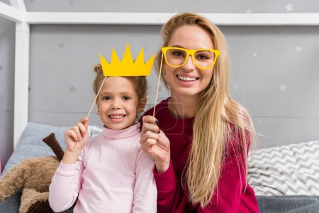smiling mother and daughter with toy masquerade crown and eyeglasses