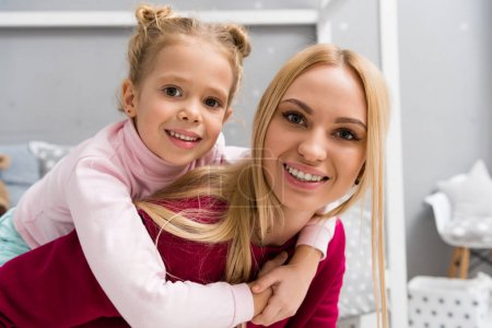happy little daughter embracing mother from behind