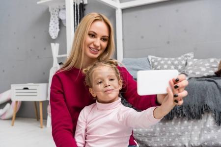 mother and daughter taking selfie in kid bedroom