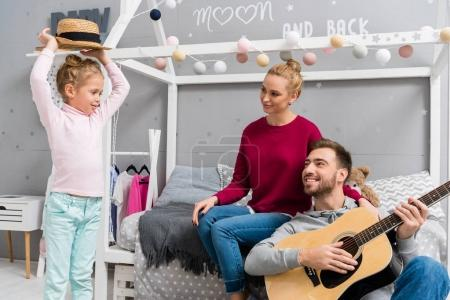 happy young father playing guitar for wife and daughter while sitting on floor at kid bedroom