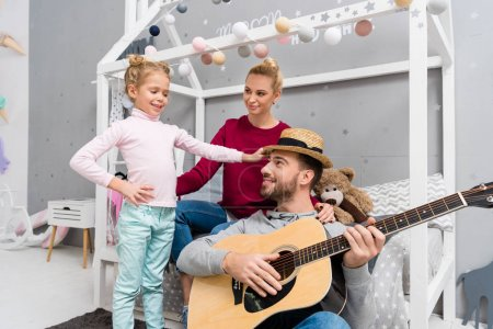 handsome young father playing guitar for wife and daughter at kid bedroom