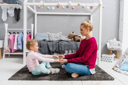 mother and daughter sitting on floor on kid bedroom and holding hands