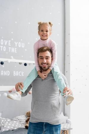 happy little daughter riding on father shoulders