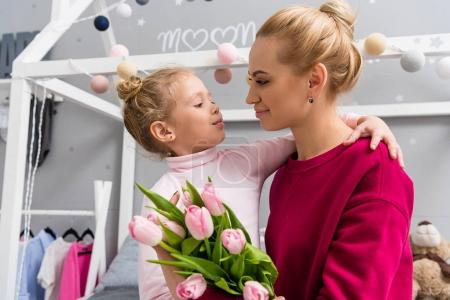 little daughter presenting tulips bouquet to mother on mothers day