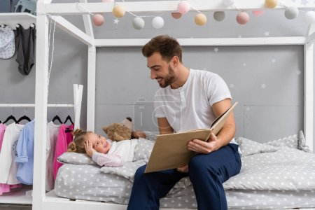 happy young father reading book for daughter in bed