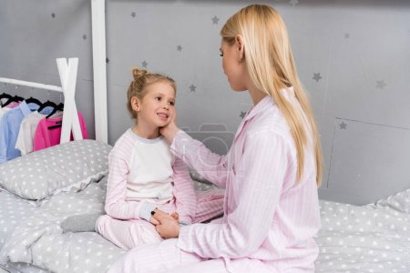 Photo for Happy mother and daughter sitting on bed in kid bedroom - Royalty Free Image