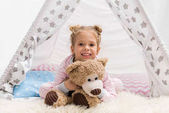 adorable little kid with teddy bear lying on floor in handcrafted teepee