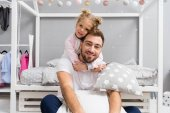 adorable daughter embracing father from behind in kid bedroom