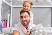 happy little daughter embracing father from behind in kid bedroom