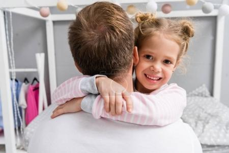 back view of adorable little daughter embracing father