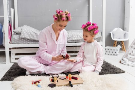 young mother painting nails of daughter with polish while they sitting in pajamas with hair rollers