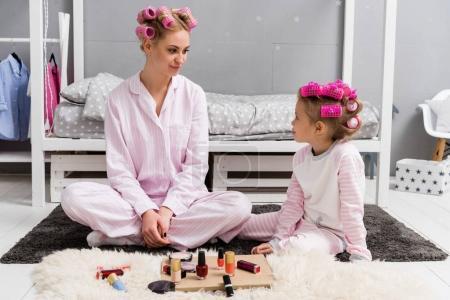 Photo pour Mère et fille en pyjama avec des rouleaux de cheveux sur la tête, assis sur le plancher - image libre de droit