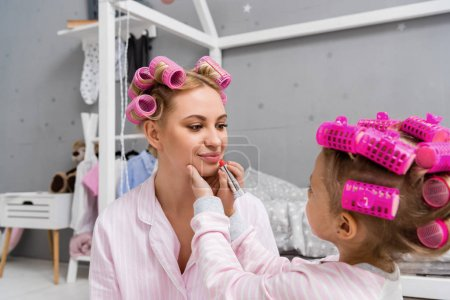 little daughter doing makeup applying lipstick on mothers lips