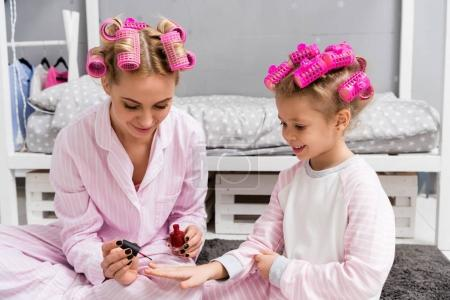 mother painting nails of daughter with polish while they sitting in pajamas with hair rollers