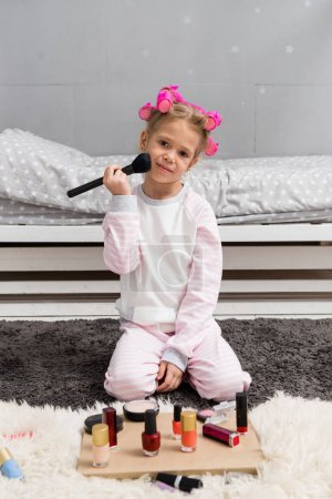 adorable little kid with hair rollers on head doing makeup with brush while sitting on floor