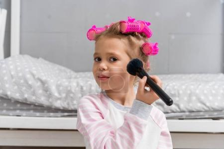 adorable little kid with hair rollers on head doing makeup with brush