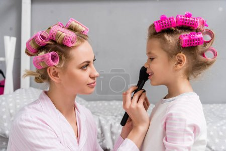 young beautiful mother and daughter with hair rollers doing makeup