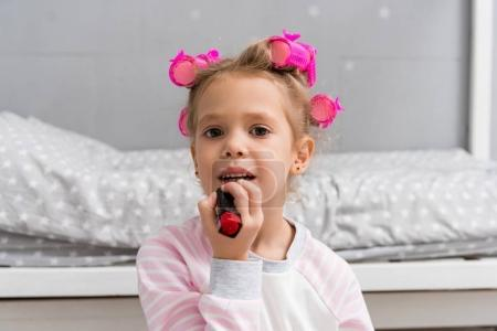 adorable little kid with hair rollers on head applying lipstick