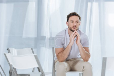 Photo for Depressed middle aged man sitting on chair and looking away in empty room - Royalty Free Image