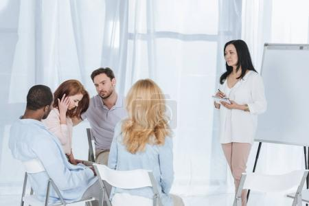 Photo for Middle aged multiethnic people supporting each other while psychotherapist taking notes during group therapy - Royalty Free Image