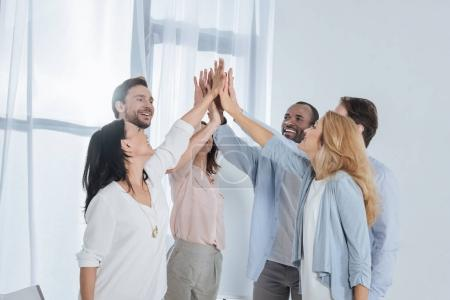cheerful multiethnic mature people giving high five during group therapy