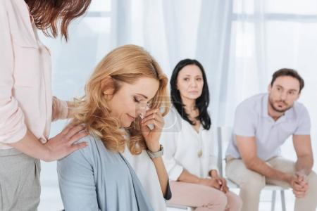 middle aged people supporting crying woman during anonymous group therapy