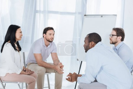 multiethnic middle aged people sitting on chairs during anonymous group therapy
