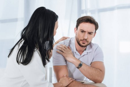 mature asian woman supporting upset man during group therapy